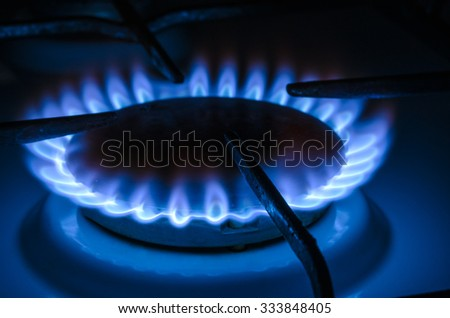 Natural gas stove heating with blue flames. - stock photo