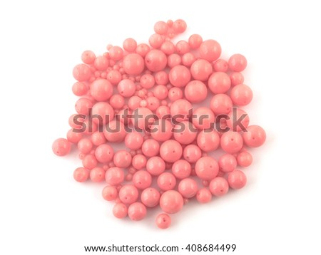 Natural gemstone pink coral beads on a white background.