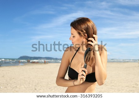 natural girl on a lonely beach brushes her healthy long hair. relaxation peace of mind and natural beauty concept   - stock photo