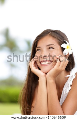Natural girl smiling and daydreaming. Cute young woman thinking happy looking up outside in summer dress with adorable flower in her brown hair. mixed race Asian Caucasian girl on Hawaii, USA. - stock photo