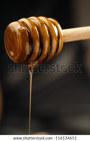 Natural golden honey oozing from a wooden drizzler
