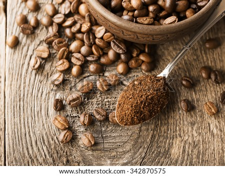 Natural ground coffee heap in transparent glass bowl on �offee grains background - stock photo