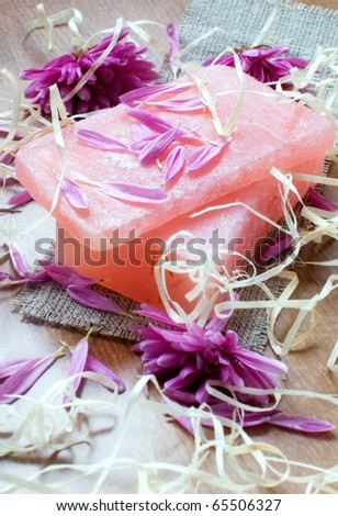 Natural hand-made soap with flowers and straw on canvas - stock photo