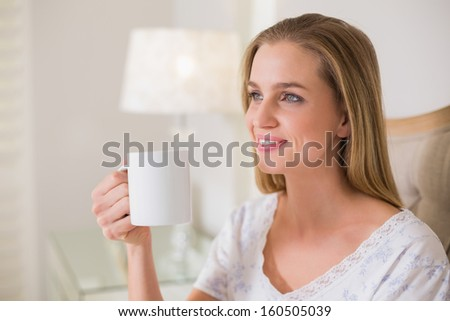 Natural happy woman sitting on bed holding mug in bright bedroom