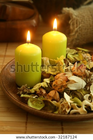 Natural herbal ingredient in wooden bowl and two candles. - stock photo