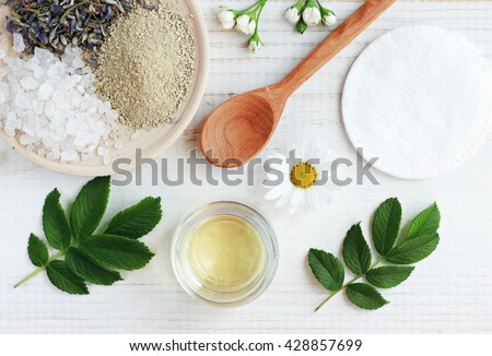 Natural herbal skin care products, top view ingredients. Cosmetic oil, clay, sea salt, herbs, plant leaves. Facial treatment preparation background.  - stock photo