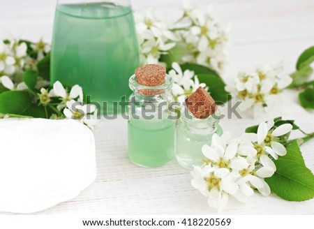 Natural herbal skincare, botanical cosmetic products. Facial tonic, essential oil, perfume in bottles, fresh flowers. - stock photo