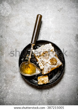 Natural honey comb with a vintage spoon. On a stone background.