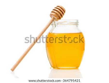 Natural honey in a glass jar, spoon for honey closeup isolated on white background - stock photo