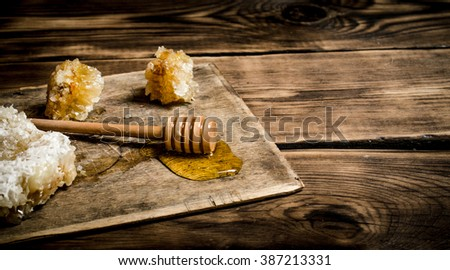 Natural honey in honeycombs with a spoon on the Board. On wooden background. - stock photo