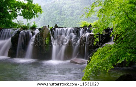 Natural hot spring bath surround by mountains - stock photo