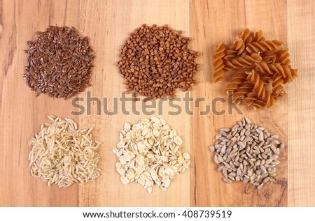 Natural ingredients and products containing magnesium and dietary fiber, healthy food and nutrition, wholemeal pasta, buckwheat, brown rice, sunflower, linseed, oatmeal - stock photo