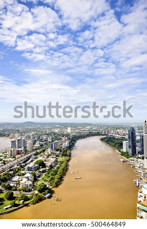 Natural lake with boats and buildings near city, smalls boats around the river, huge buildings and apartments have in the city, highway bridge is fulled with vehicles, sky is clear with white clouds.