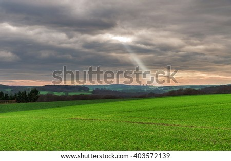 Natural landscape with sun rays and clouds - stock photo