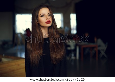 Natural light indoor portrait of young pretty girl with long dark brown hair, natural makeup and red lips. Stylish woman looking at you - stock photo