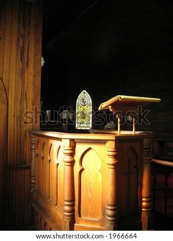 natural light of very old stained glass windows falls across the antique lectern in this historic  little church, built in early 1800s - stock photo