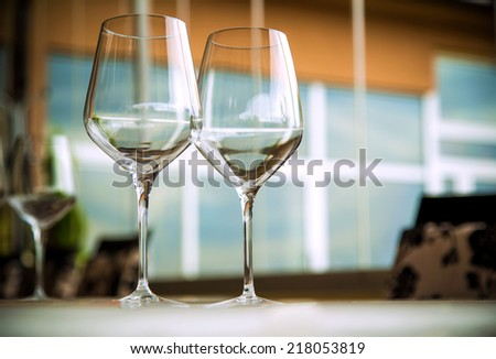 Natural light or daylight shot of modern restaurant table set for a lunch. Shallow focus on wine glass - stock photo