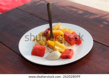 Natural light photo of different fruit mix salad on white plate view 3 - stock photo