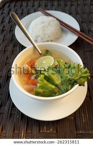Natural light photo of lemongrass seafood soup with steamed rice, shallow DOF view 1 - stock photo
