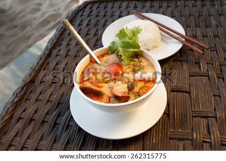 Natural light photo of Tom Yam seafood soup served with rice, shallow DOF seaside view 2 - stock photo