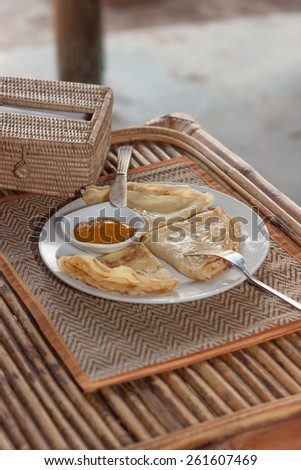 Natural light photo with shallow DOF of crepes with mango jam, tableware and rattan napkin holder on mat and a wooden table view 1 - stock photo