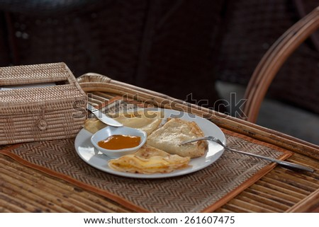 Natural light photo with shallow DOF of crepes with mango jam, tableware and rattan napkin holder on mat and a wooden table horizontal view - stock photo