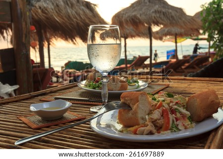 Natural light photo with shallow DOF of romantic beach evening on the sunset with glass of water and dinner horizontal view 2 - stock photo