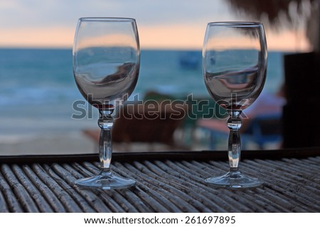 Natural light photo with shallow DOF of romantic beach evening on the sunset with two glasses horizontal view 3 - stock photo