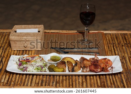 Natural light photo with shallow DOF of seafood mix barbecue with salad and glass of wine on plate on bamboo table view 2 - stock photo