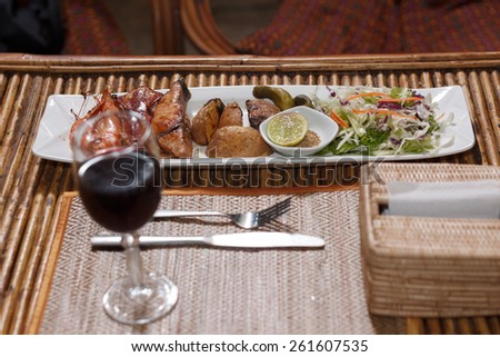 Natural light photo with shallow DOF of seafood mix barbecue with salad and glass of wine on plate on bamboo table view 1 - stock photo
