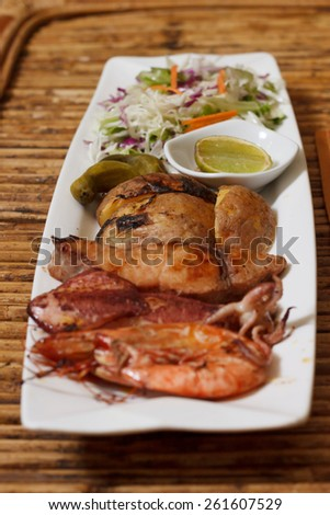 Natural light photo with shallow DOF of seafood mix barbecue with salad on plate on bamboo table - stock photo