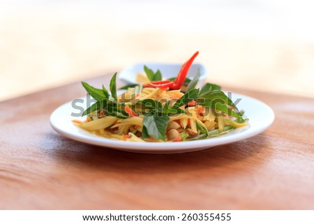 Natural light photo with shallow DOF of spicy green mango salad on a wooden table - stock photo