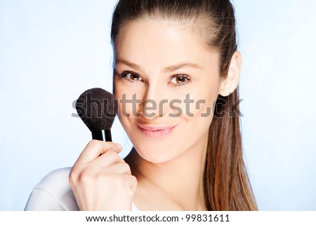 natural looking young woman hold cosmetics brush studio shot - stock photo