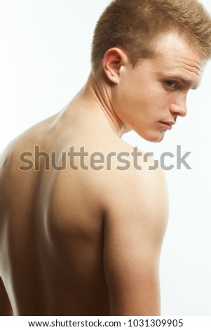 Natural male beauty concept. Close up portrait of handsome charismatic young man's back posing over white background. Studio shot