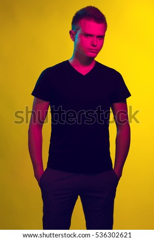 Natural male beauty concept. Pop-art portrait of handsome charismatic man posing over yellow background in black t-shirt. Hands in pockets. Stylish modern haircut. Studio shot
