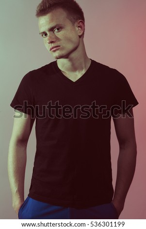 Natural male beauty concept. Portrait of handsome charismatic man posing gray background in black t-shirt. Hands in pockets. Stylish modern haircut. Studio shot