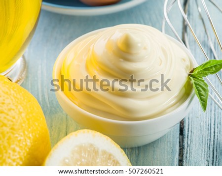 Natural mayonnaise in the white bowl and lemons.