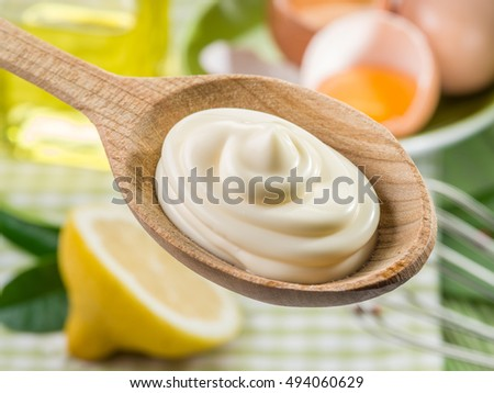 Natural mayonnaise sauce in the wooden spoon and its ingredient on the background.
