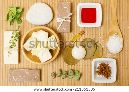 natural moisturizer, bath salt, soaps, dried st johns wort and red oil from hypericum perforatum on bamboo background - stock photo