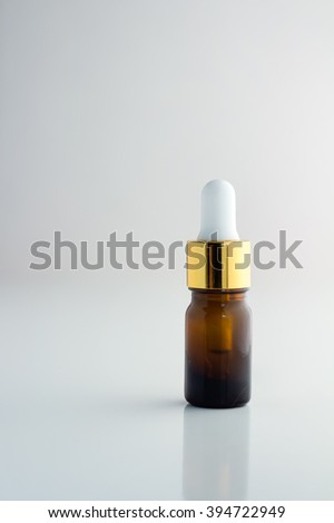 Natural organic oil bottle on white background. Body oil in brown bottle. - stock photo