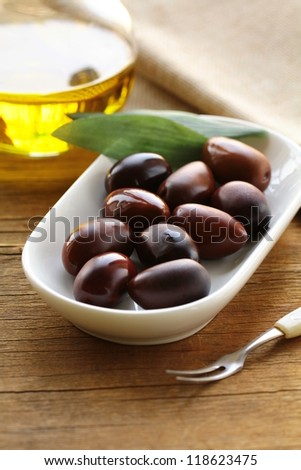 natural organic olives in a white bowl, a bottle of oil in the background - stock photo