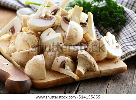 natural organic raw mushrooms champignons on a wooden table