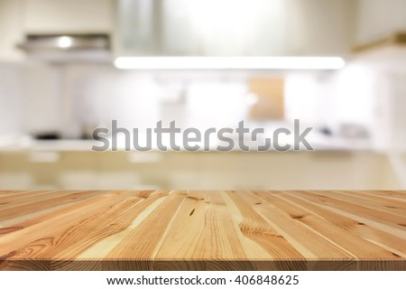 Natural pattern wood table top (or kitchen island) on blur kitchen interior background - can be used for display or montage your products - stock photo