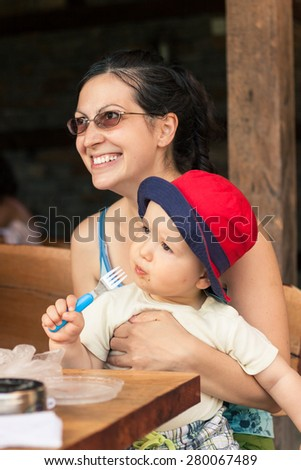 Natural photo of a smiling woman holding her baby while he eats with a fork. - stock photo