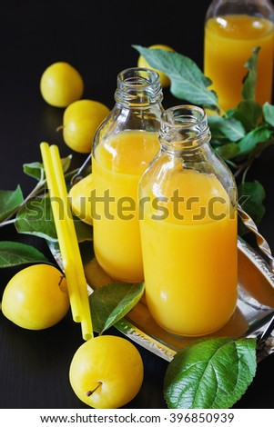 Natural plum juice in a bottle of yellow plums on a black wooden background. Bio healthy food and drink concept. Selective focus - stock photo