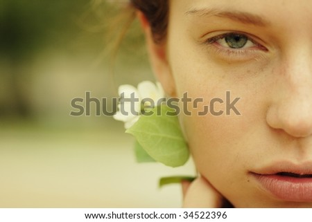 natural portrait of a beautiful young woman with a flower