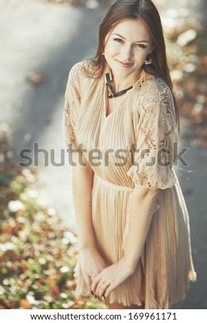 Natural portrait of young beautiful woman outside. Caucasian woman with long hair wearing dress on sunny summer day. - stock photo