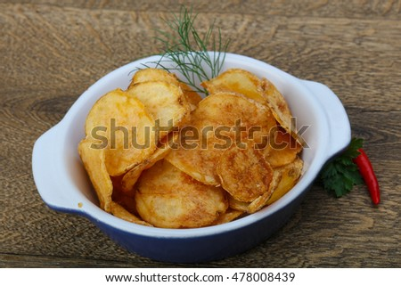 Natural potato chips heap in the bowl on wood background