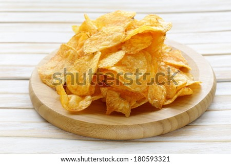 natural potato chips with paprika in a bowl on a wooden table - stock photo