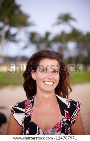 Natural  pretty woman walking on beach (warm breeze blowing hair) tropical palm trees in background - stock photo